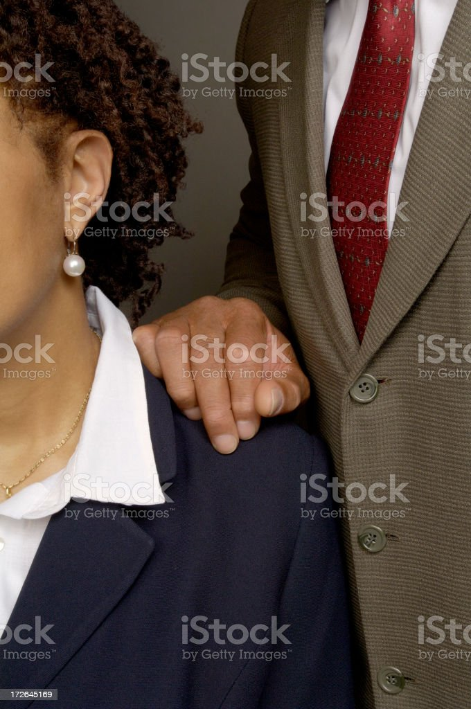 Male employee inappropriately touching female co-worker stock photo