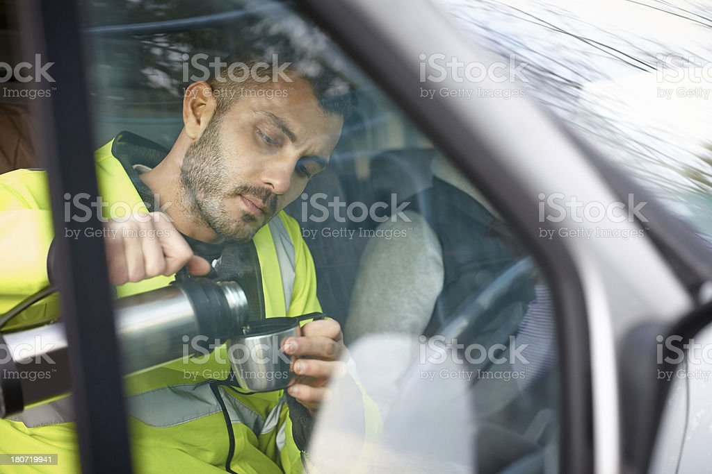 Male engineer having a cup of coffee in his car stock photo