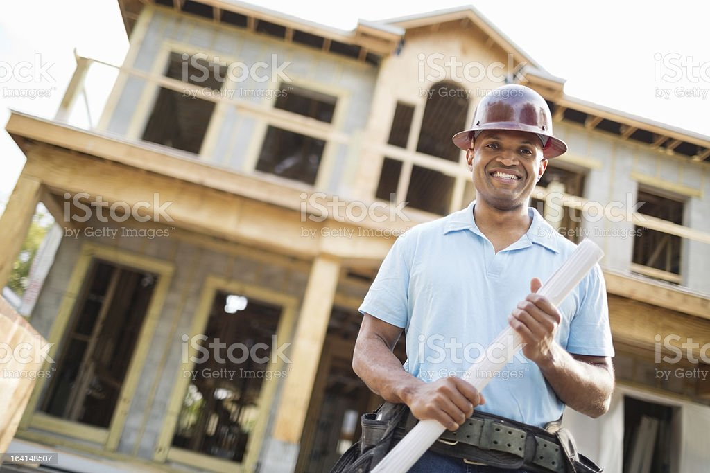 Male Engineer With Blueprint Against Incomplete House royalty-free stock photo