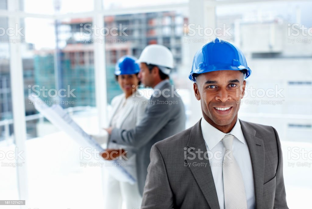Male engineer with colleagues in the background royalty-free stock photo