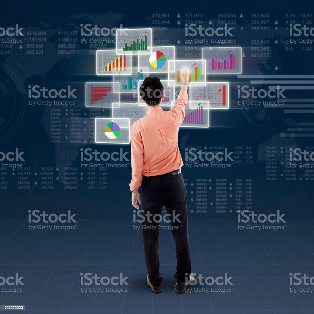 Male entrepreneur touching financial chart stock photo