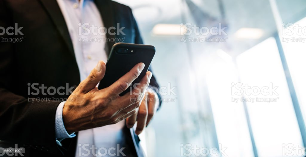 Male entrepreneur with mobile phone in office stock photo