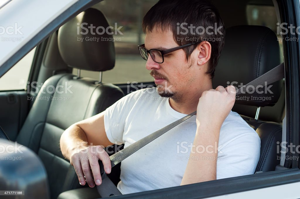 Male european driver is using seat belt in a car stock photo