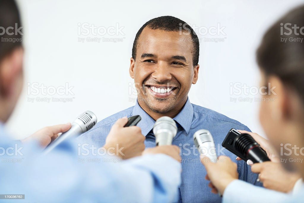 Male executive being questioned by journalists. stock photo