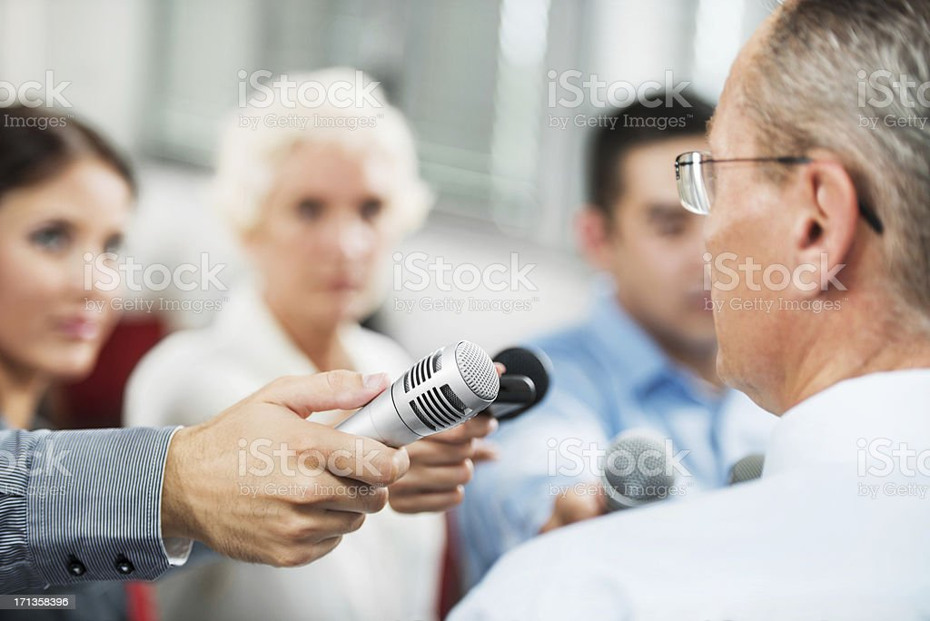Male executive being questioned by journalists stock photo