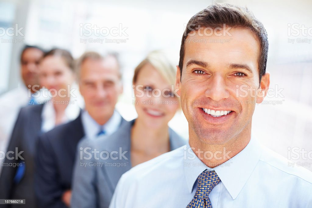 Male executive smiling with his colleagues standing in a row royalty-free stock photo