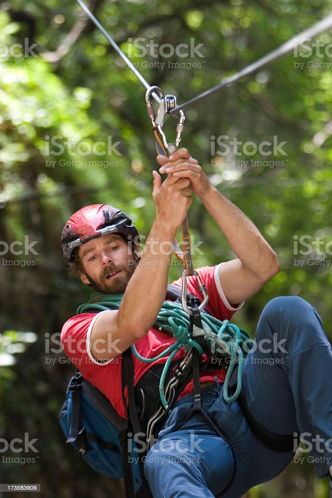 Male extreme sports enthusiast zip lining through forest stock photo
