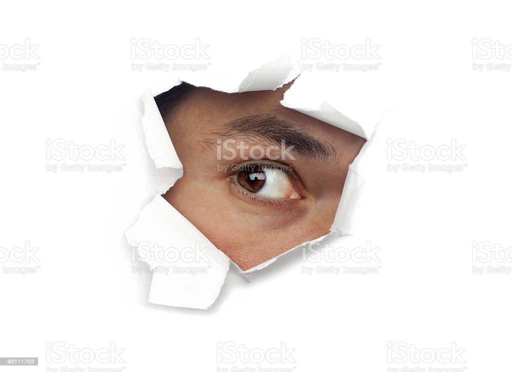 Male Eye Staring Out Of Hole of Ripped White Paper stock photo