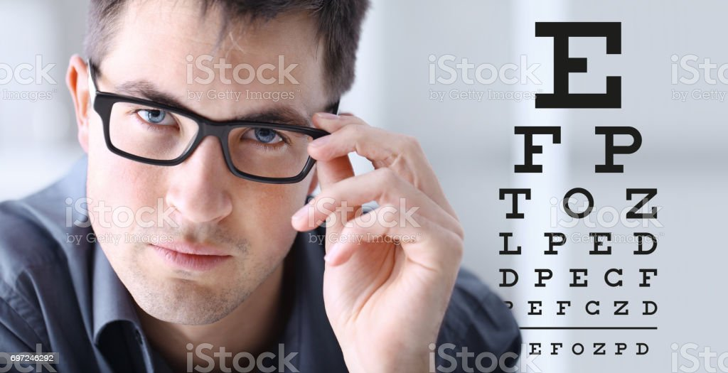 male face with spectacles on eyesight test chart background, eye...