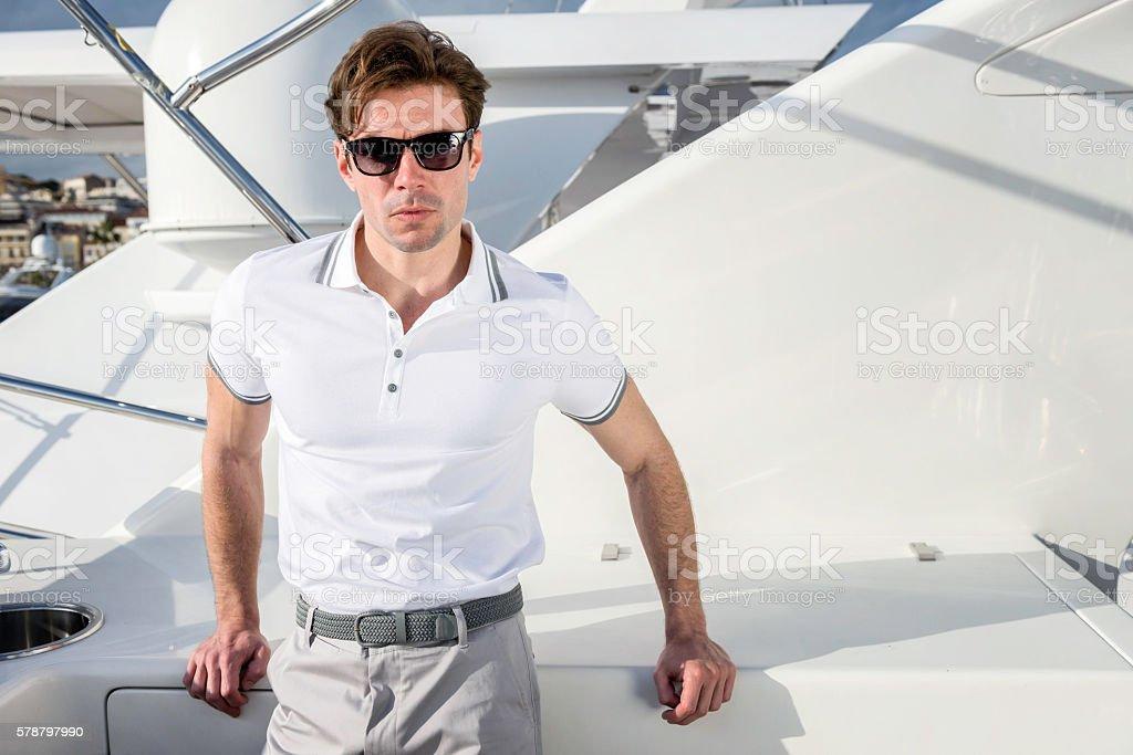 Male fashion model on yacht stock photo