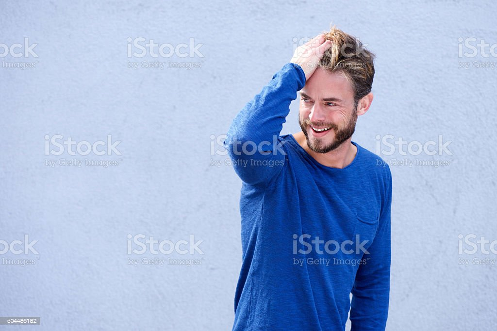 Male fashion model smiling with hand in hair stock photo