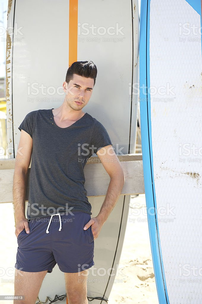 Male fashion model standing outdoors with surfboards royalty-free stock photo