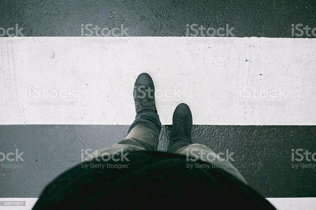 Male feet crossing the street on crosswalk art filter stock photo