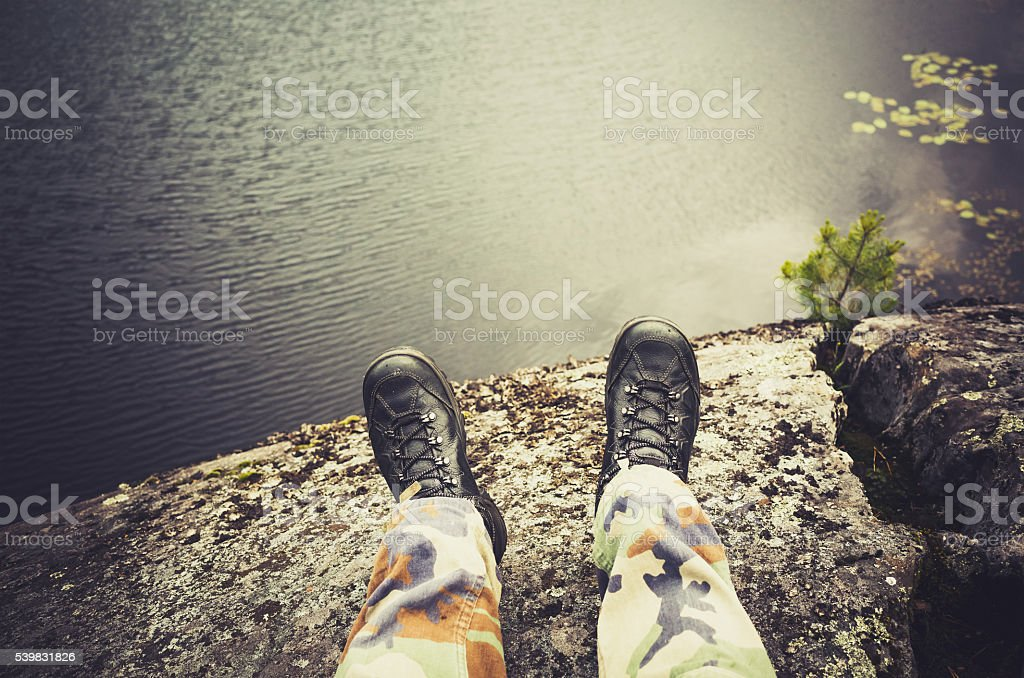 Male feet in camouflage pants and black shoes stock photo