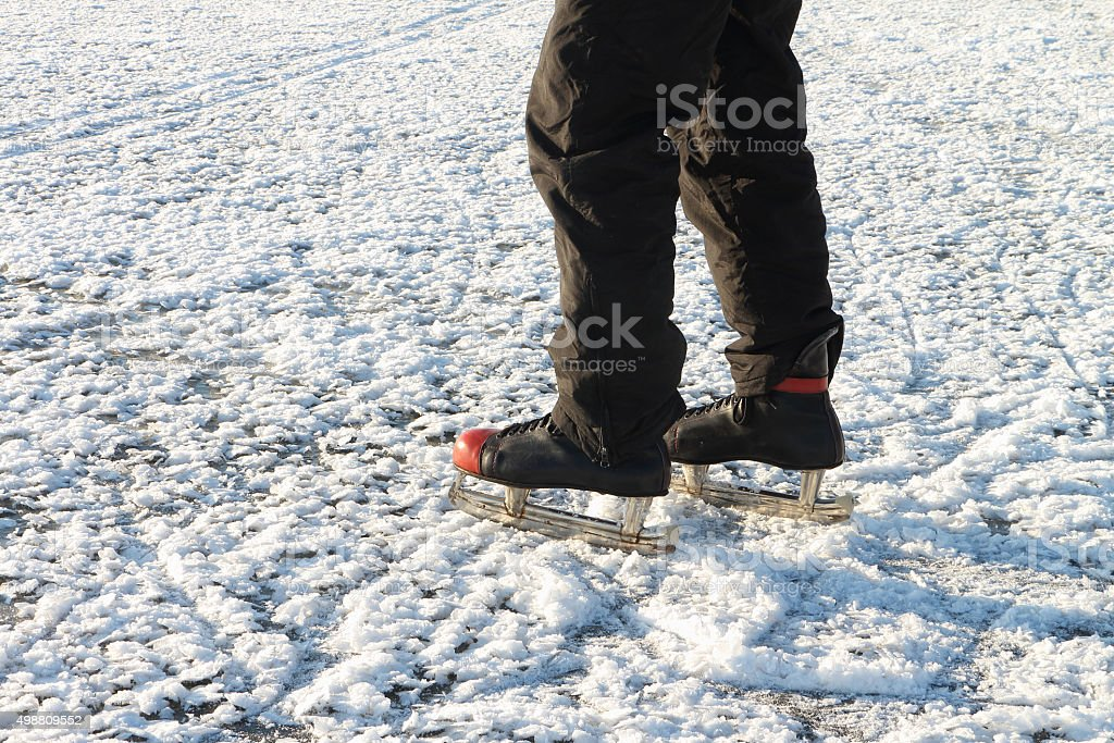 Male feet in the skates on a snow surface stock photo