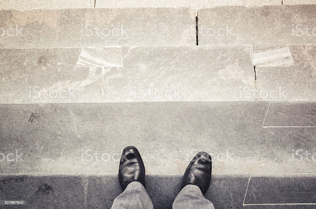 Male feet stand on outdoor stone stairs stock photo