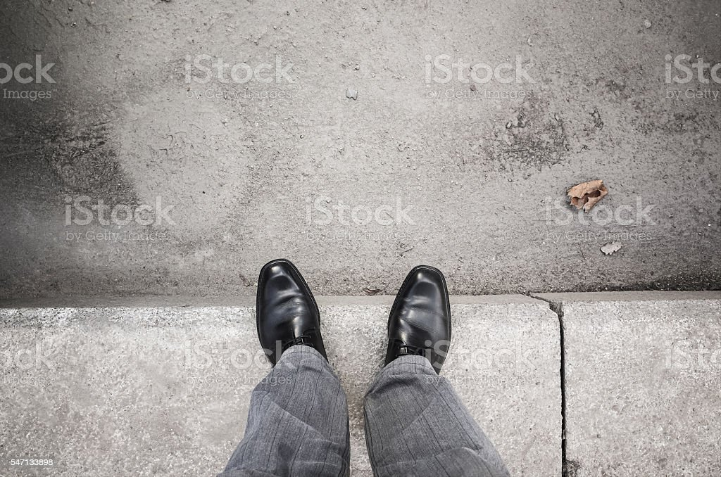 Male feet standing on gray curb stock photo