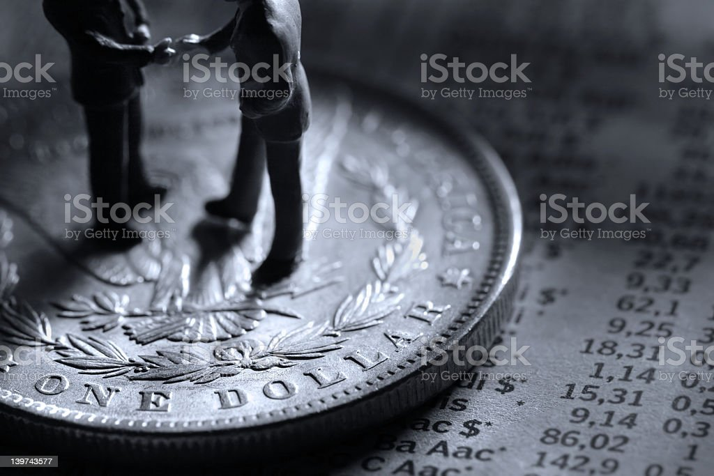 Male figures shaking hands on an oversized dollar coin royalty-free stock photo