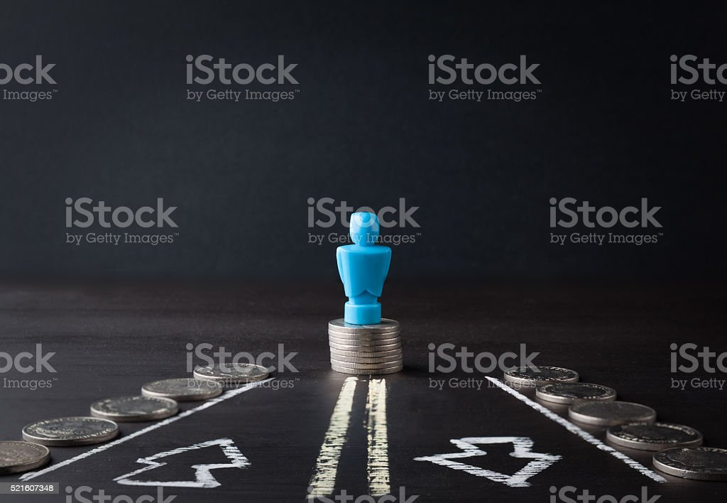 Male figurine standing on pile of coins stock photo