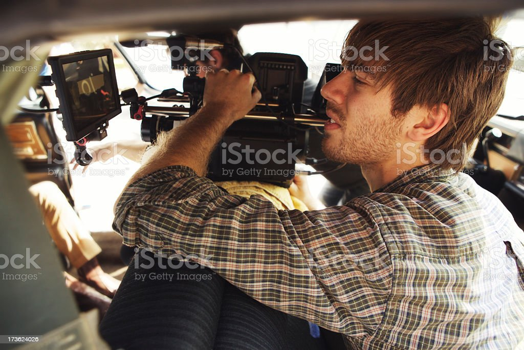 A male filming with a camera for production stock photo
