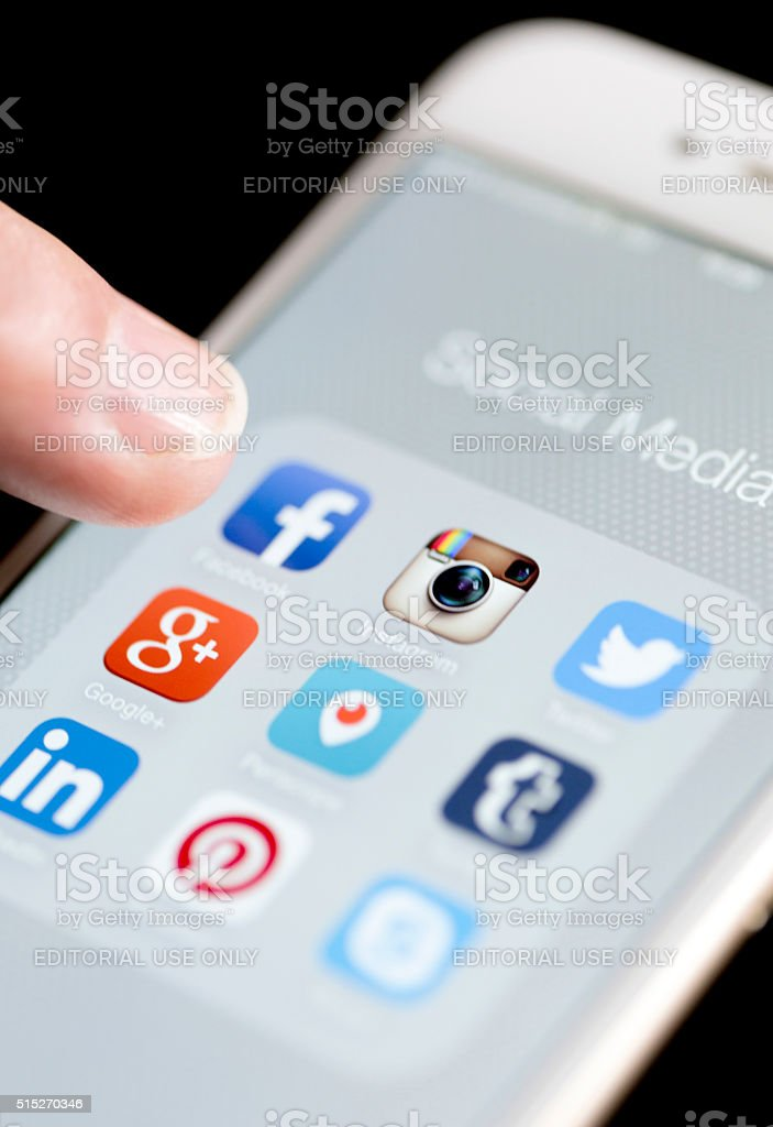 Male Finger is Touching Facebook App on iPhone 6 stock photo
