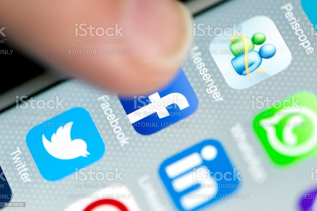 Male Finger is Touching Facebook App on iPhone 6 Screen stock photo