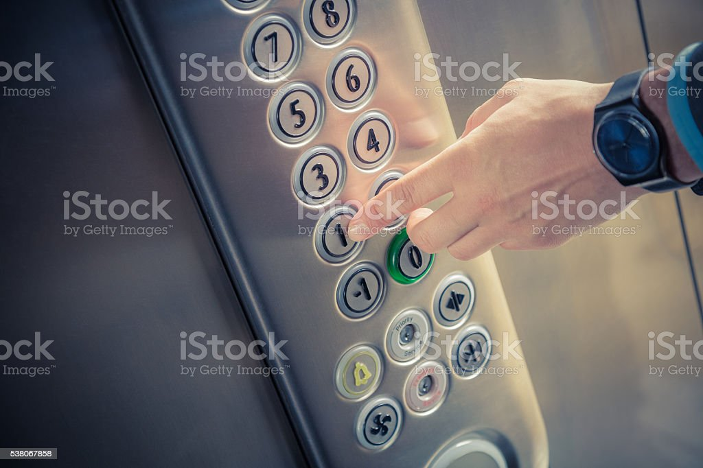 Male finger pressing the first floor button in the elevator stock photo