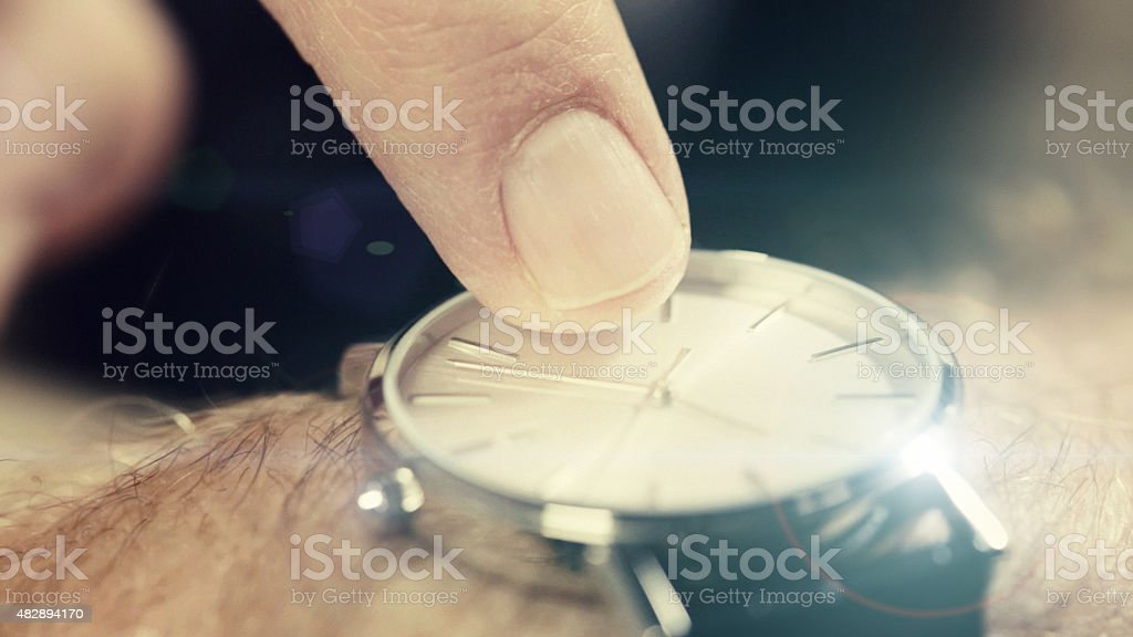 Male finger tapping watch face, indicating time pressure or impatience stock photo
