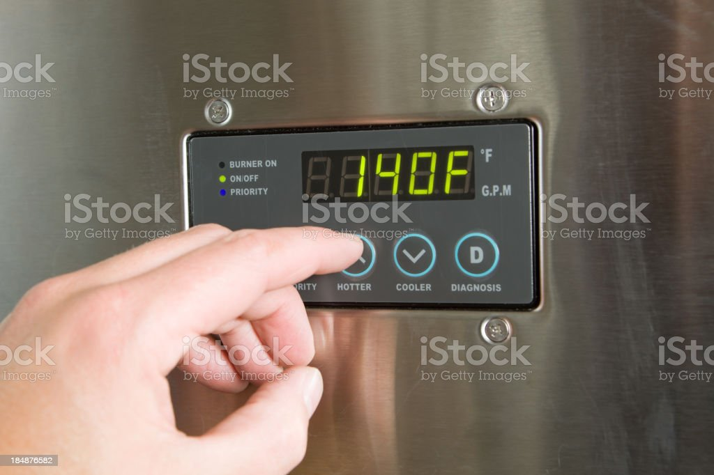 Male Finger Turning Up Tankless Water Heater Temperature royalty-free stock photo