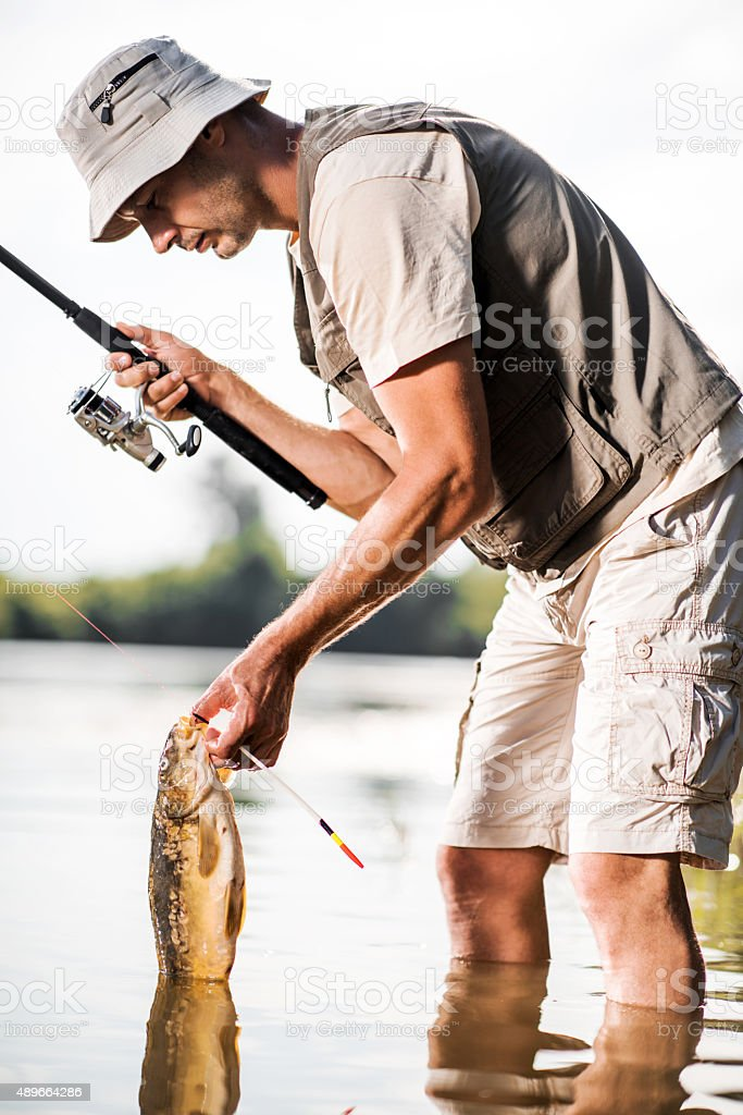Male fisherman caught a common carp on the river. stock photo