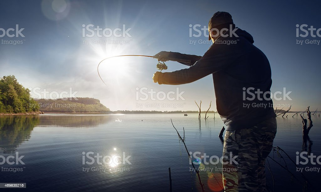 Male fishing at sunset on lake stock photo