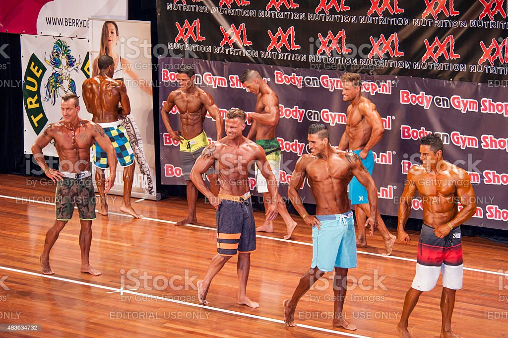 Male fitness contestants show their physique in a lineup stock photo