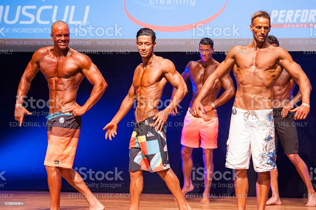 Male fitness models show their physique in swimsuit om stage stock photo