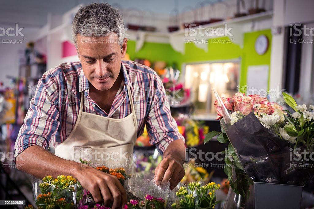 Male florist arranging bouquet of flower stock photo