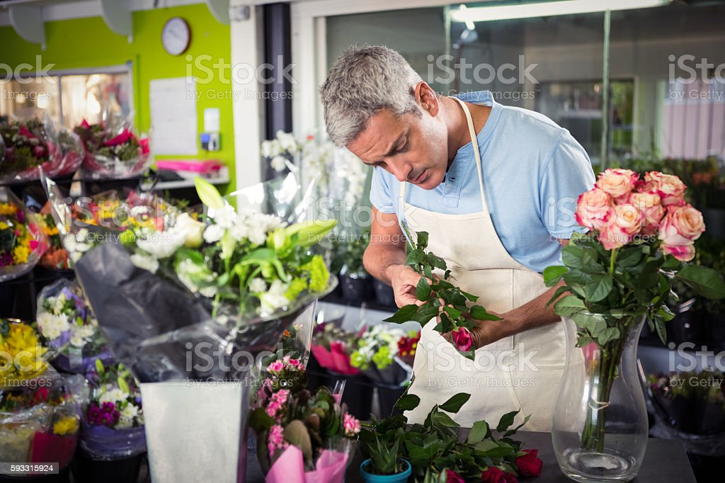 Male florist arranging flowers stock photo