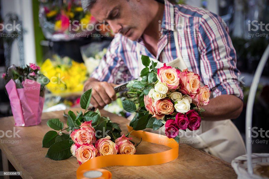 Male florist preparing bouquet of flower stock photo