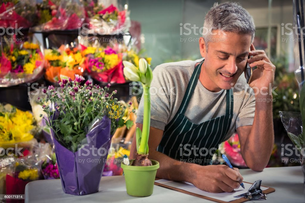 Male florist taking order on mobile phone stock photo