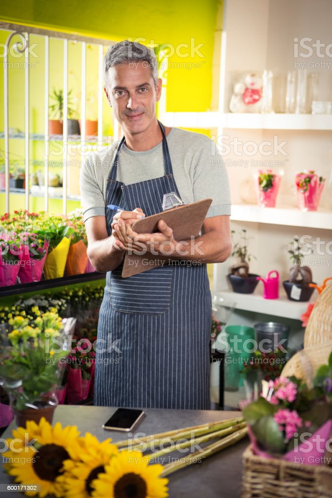 Male florist writing on clipboard stock photo