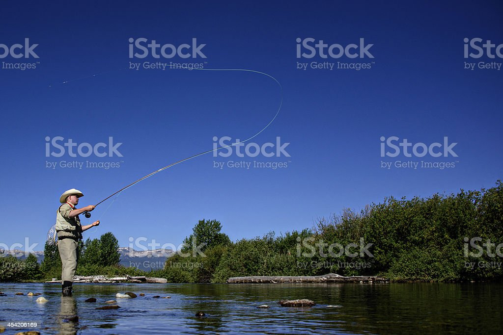 Male flyfisherman in mountain stream stock photo