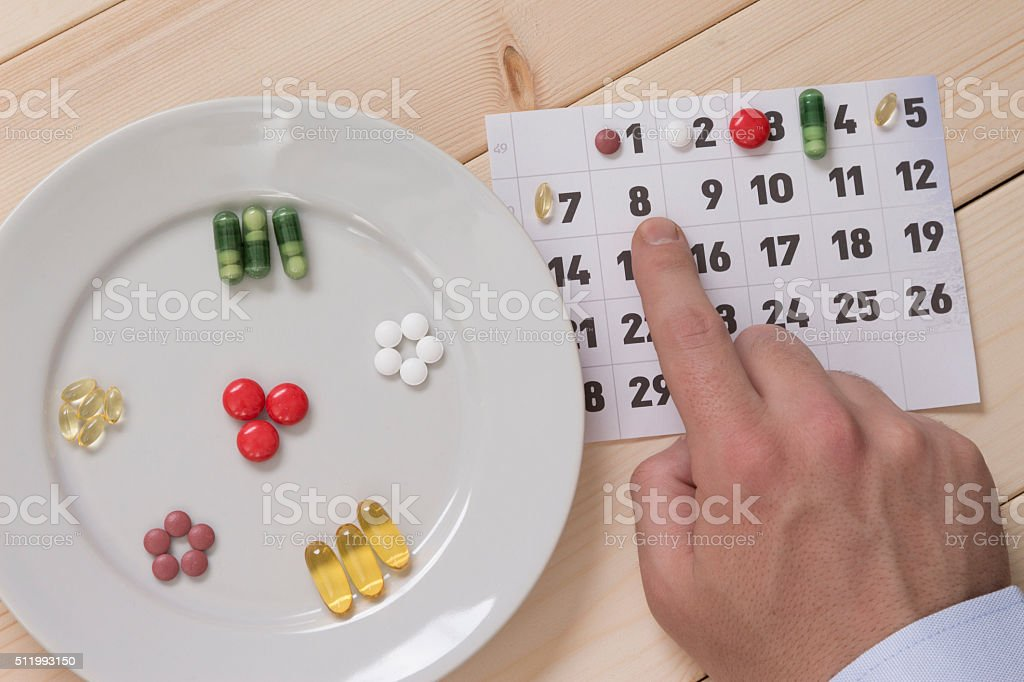 Male forefinger showing the therapy schedule on the calendar stock photo