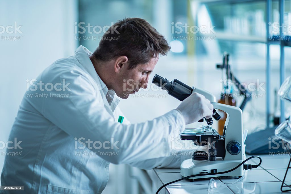 Male forensic scientist examining something through a microscope. stock photo
