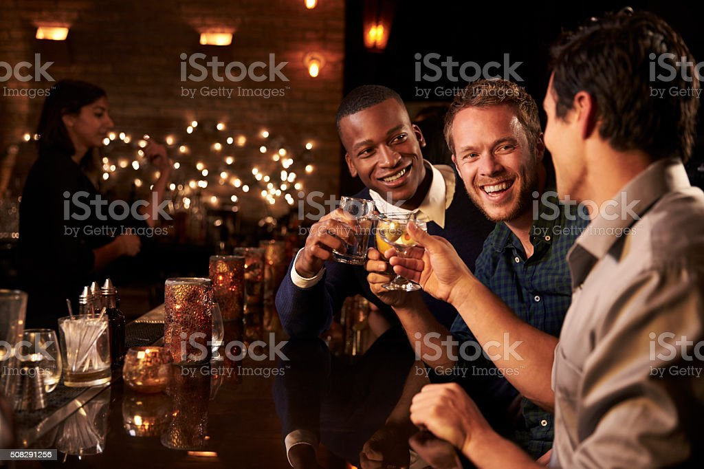 Male Friends Enjoying Night Out At Cocktail Bar stock photo