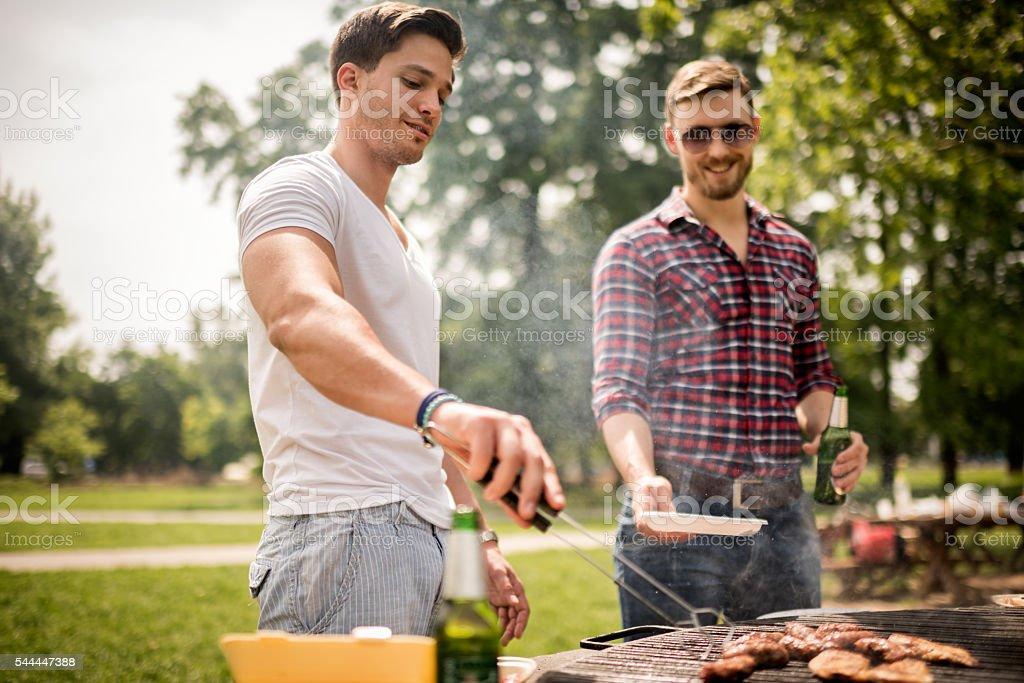 Male friends on a barbecue picnic stock photo