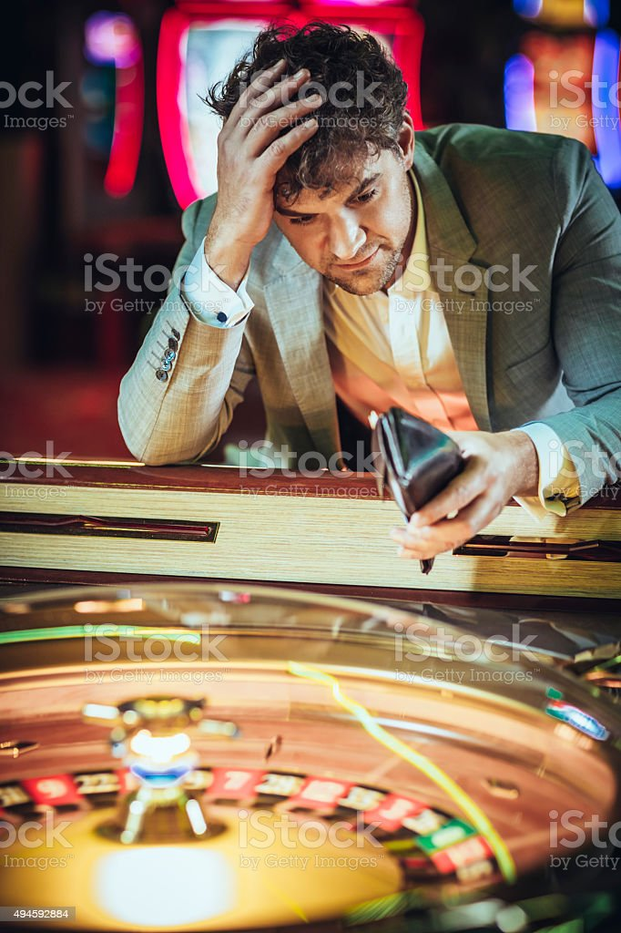 Male gambler losing at electronic roulette in  casino stock photo