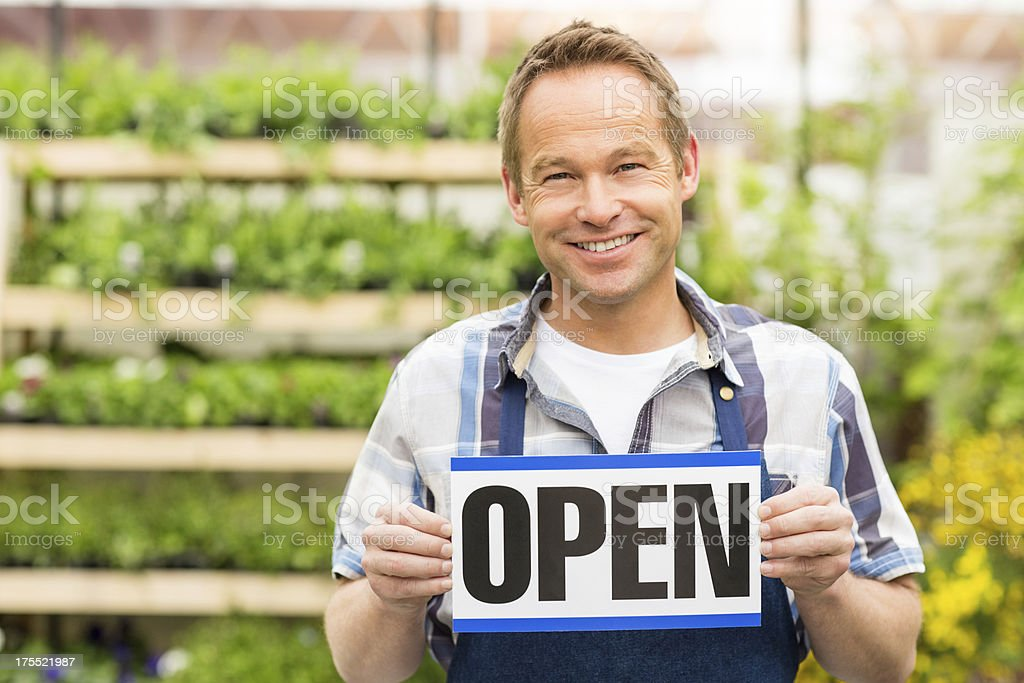 Male Garden Worker Holding an Open Signboard royalty-free stock photo