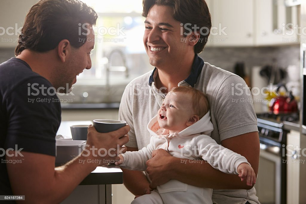Male gay couple holding baby girl in their kitchen stock photo
