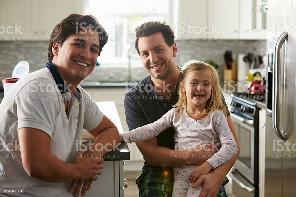Male gay couple sitting with their daughter in the kitchen stock photo