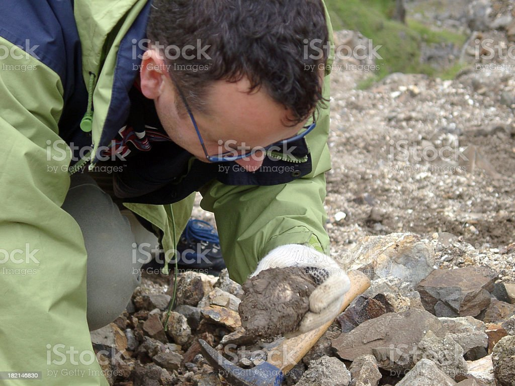 male Geologist scientist man looking at rock sample in quarry stock photo