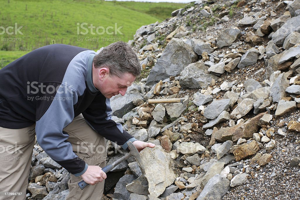 male Geologist scientist with hammer examining rocks stock photo