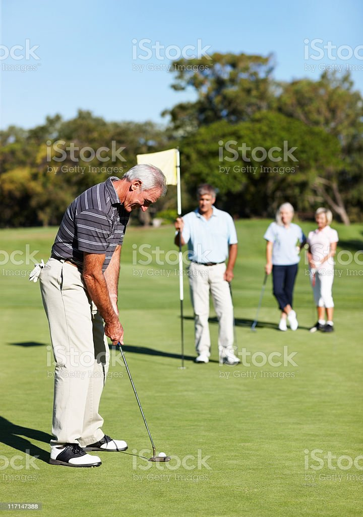 Male golf player putting royalty-free stock photo
